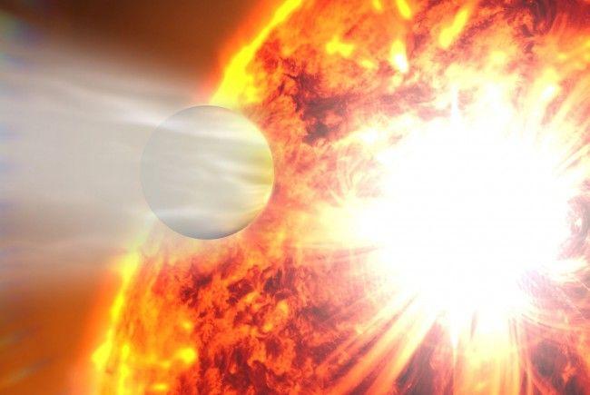 Diese künstlerische Darstellung illustriert, wie die Atmosphäre des Exoplaneten HD 189733b infolge einer gewaltigen Strahleneruption seines Heimatsterns verdampft.