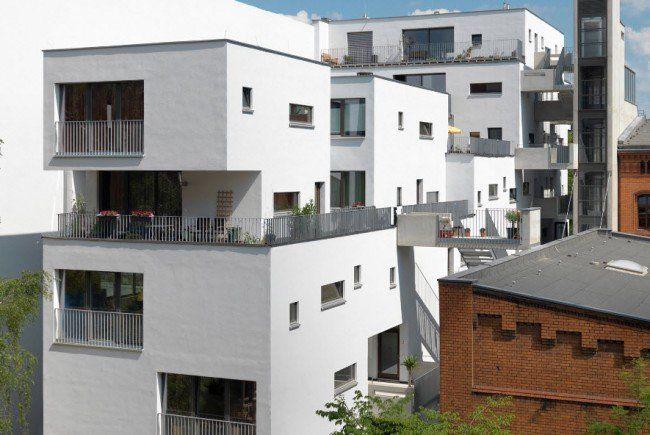 Bild eines der holzhäuser unmittelbar am hochhaus der lettischen