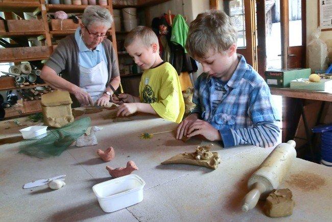 Kinder beim Modellieren von kleinen Kunstwerken aus Ton im Schlosserhus.