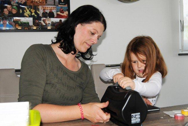 Ronja bedient voller Eifer die Prägepresse für Bastelkarton, Mama Simone unterstützt sie